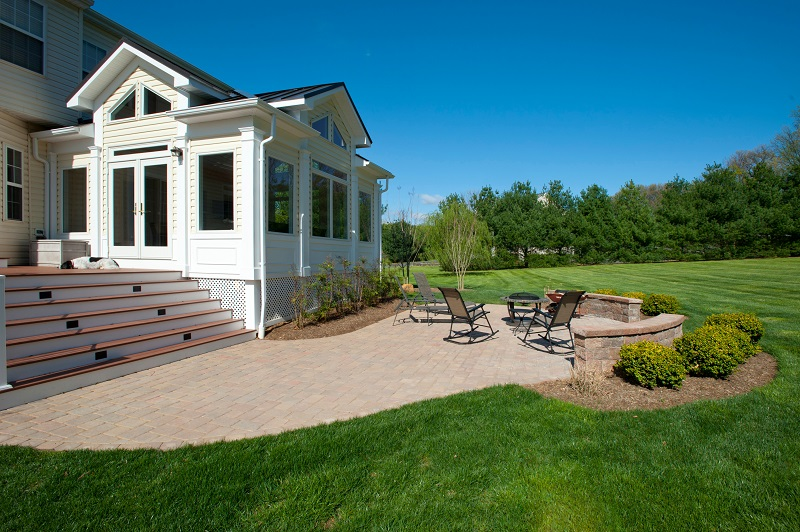 Belgard Patio, Azek Deck, and Sun Room Addition Built in Damascus, Maryland by Design Builders, Inc.