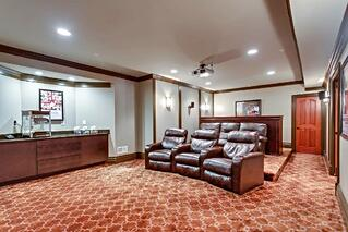 entertaining room for a private residence with leather chairs and red movie theater carpet