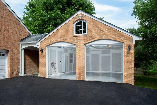 brick garage home addition with blut skies and a well-manicured lawn