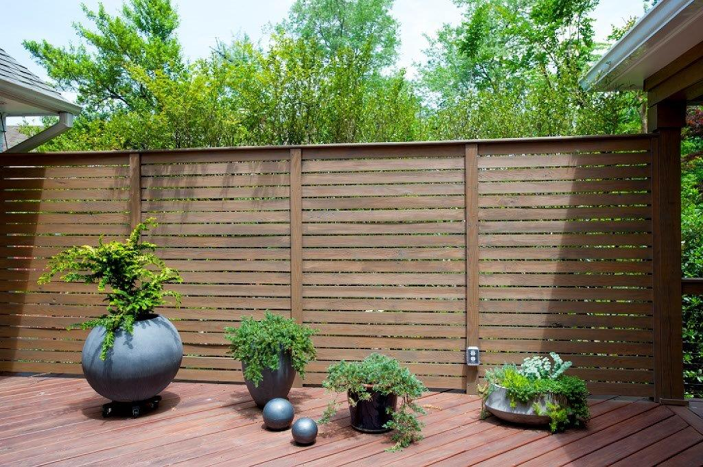 contemporary hardwood privacy fence with plant decorations