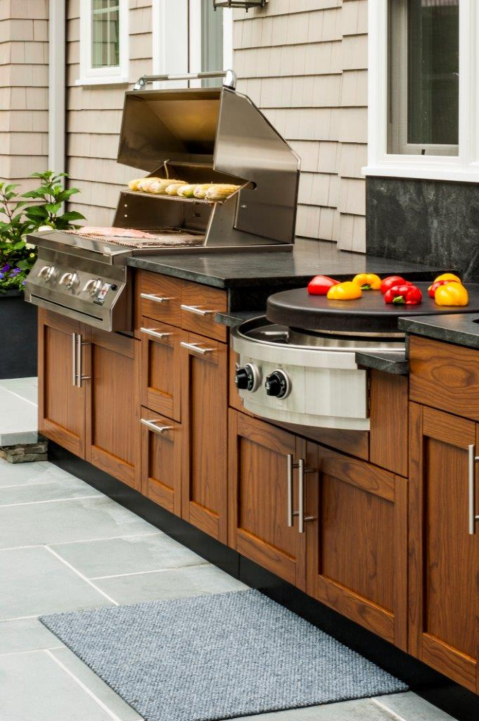 Danver outdoor kitchen cabinets outfitted with backyard cooking and grilling appliances
