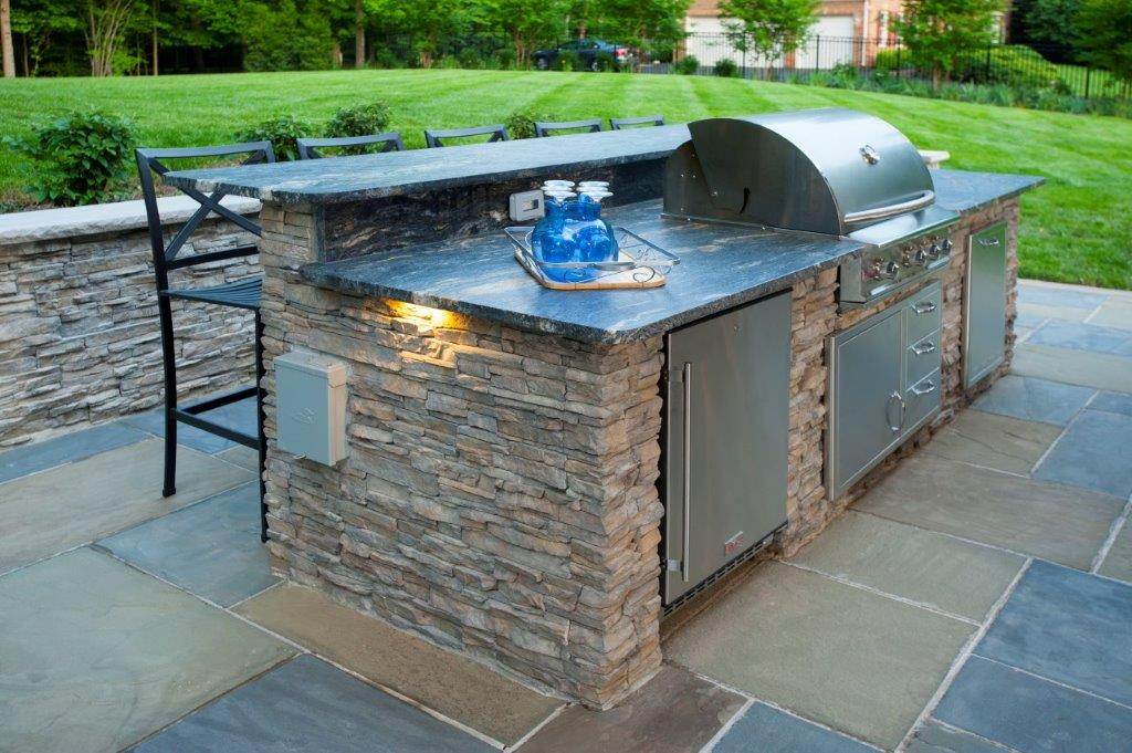 outdoor kitchen island with Blaze grill, trash pull, and stainless steel appliances