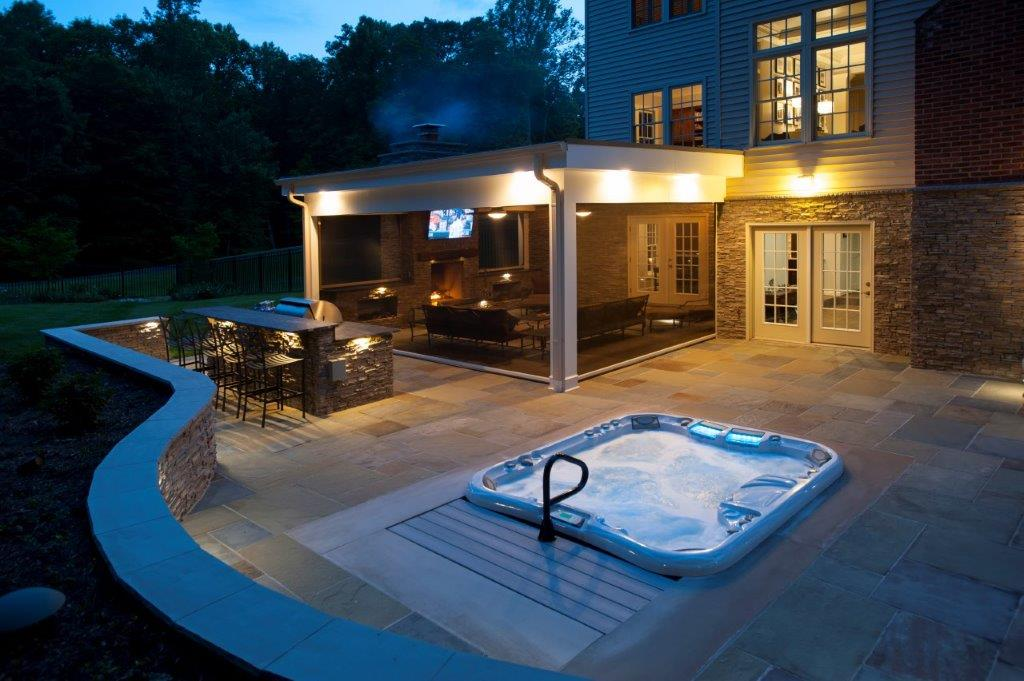 curved flagstone patio, recessed hot tub, and Phantom retractable screened potio at night Clifton, VA (1).jpg