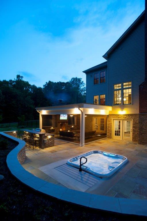 outdoor kitchen in Virginia at night with recessed hot tub