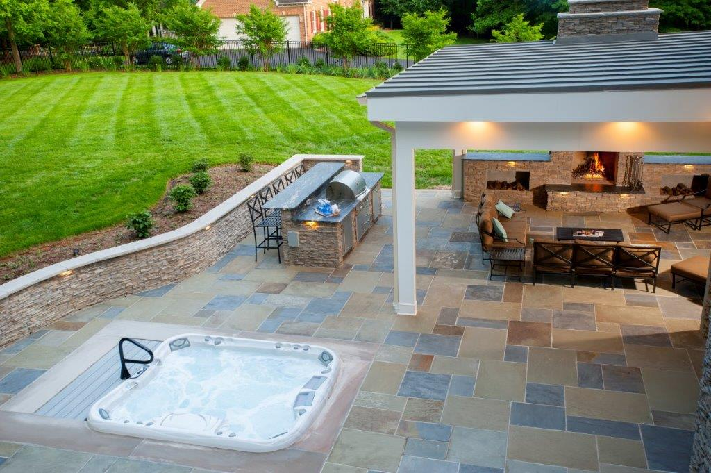hot tub recessed in custom flagstone patio with curved sitting wall in Clifton, Virginia