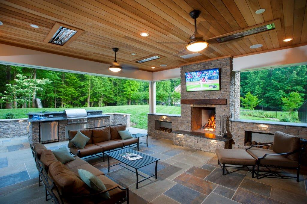 covered flagstone patio with backyard fireplace and mounted outdoor television in Virginia