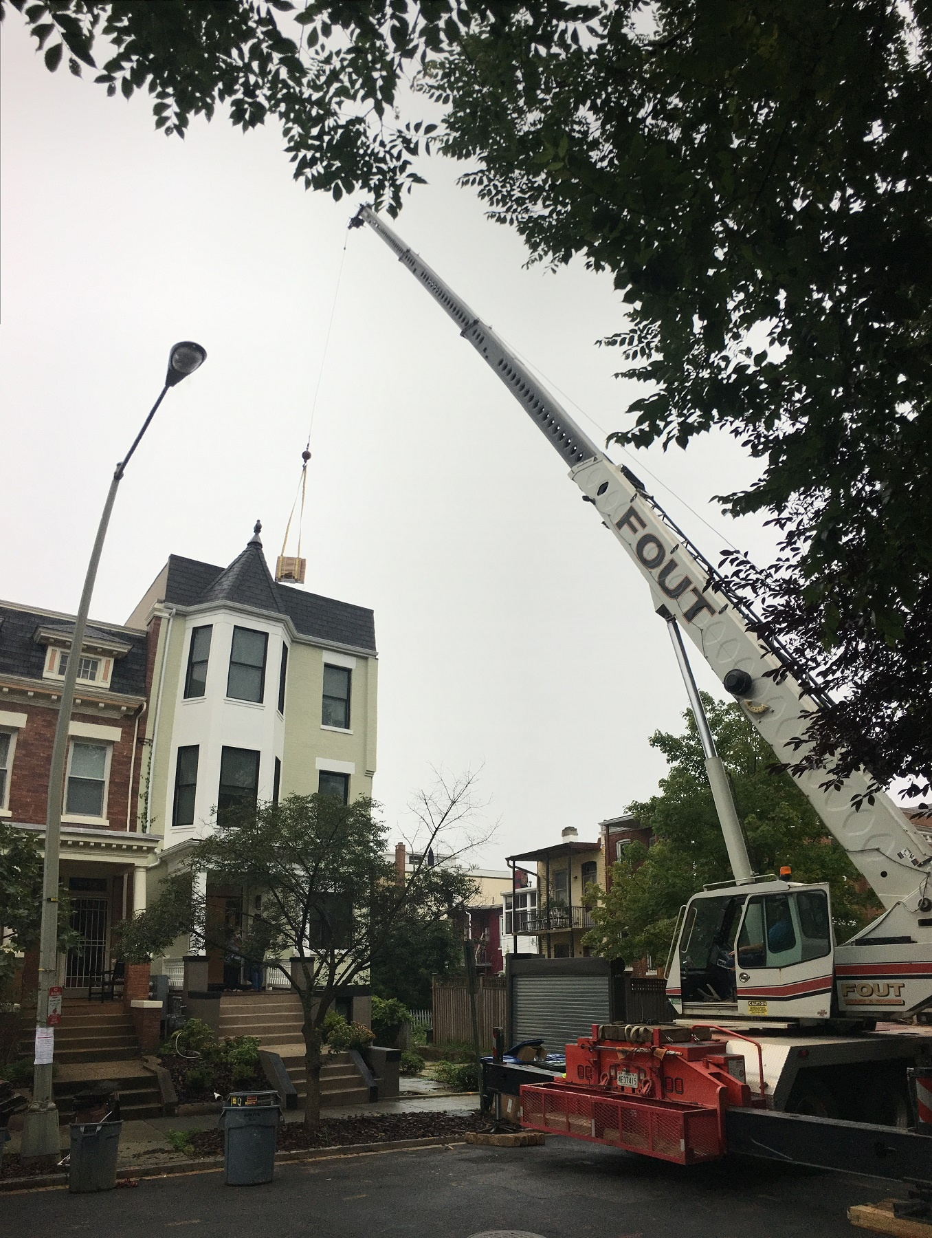 crane rental closing a street in Washington, DC to move supplies from the ground to the roof.
