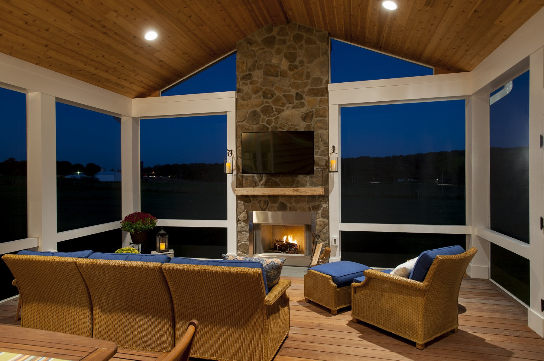 low-voltage lighting in a screened porch with a fireplace at night