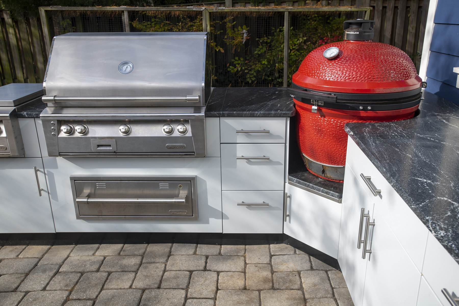 close up of Danver stainless cabinets with green egg smoker, granite countertops and stainless grill