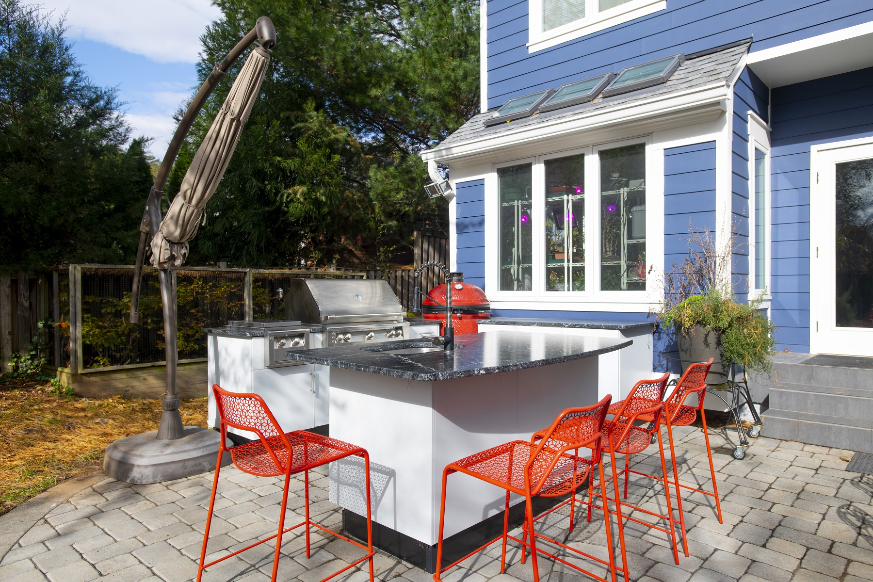 three quarter view of white powder coated stainless outdoor kitchen cabinetry with dark granite countertops in daylight