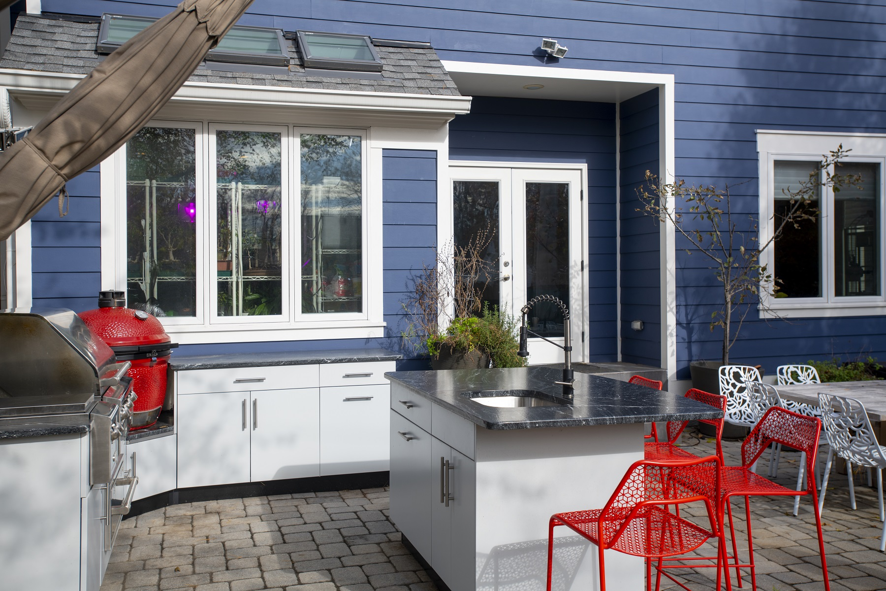 outdoor kitchen design in virginia with white powder coated cabinetry and a red green egg smoker