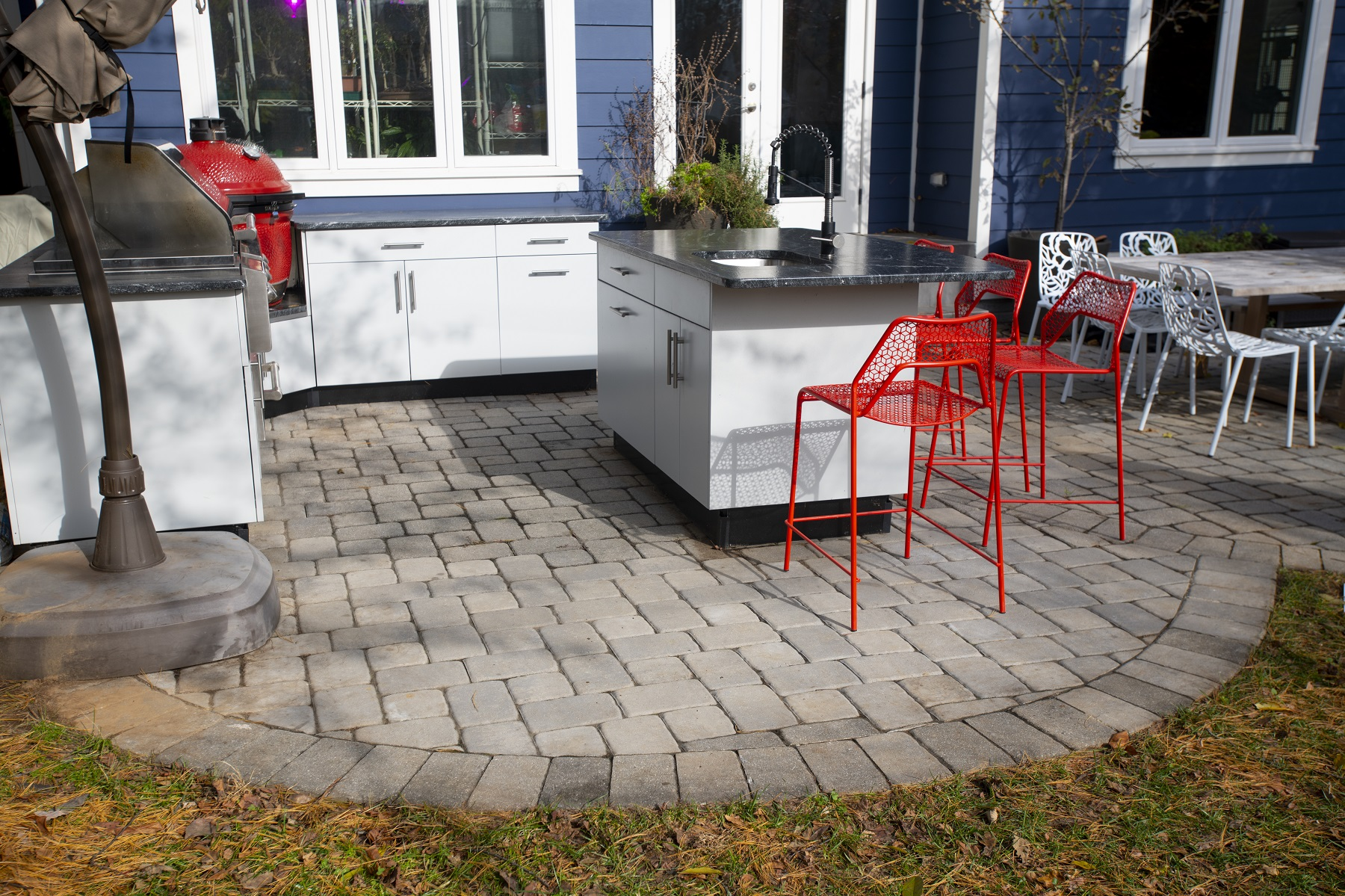 white outdoor kitchen cabinetry with bright orange chairs in falls church, virginia