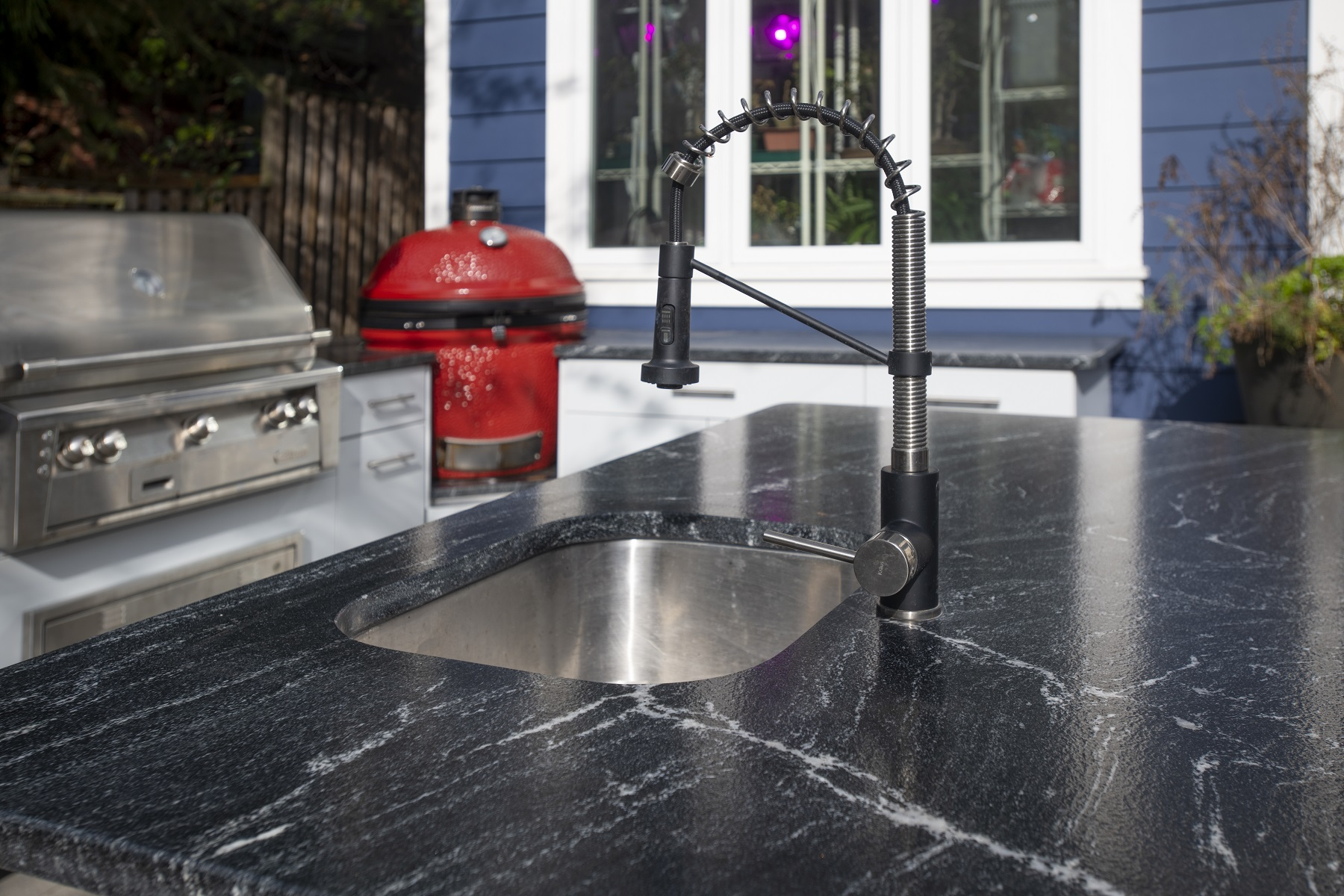 stainless sink for an outdoor kitchen with red green egg smoke and stainless steel grill in the background